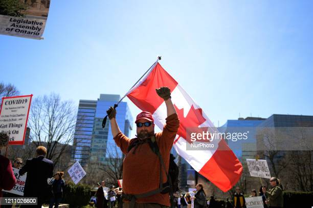 A protester waiving Canadian Flag during a rally to protest provincial and federal shut down to control the spread of Codid19 at Queens Park in...