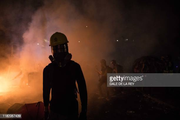 A protester walks amongst tear gas and smoke from a burning barricade during clashes with police at the Chinese University of Hong Kong in Hong Kong...