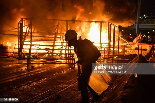 TOPSHOT A protester walks before a barricade they set on fire in the Wan Chai district in Hong Kong on August 31 2019 Chaos engulfed Hong Kong's...