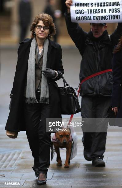 A protester walks behind Vicky Pryce the exwife of former cabinet minister Chris Huhne as she arrives at Southwark Crown Court on February 14 2013 in...