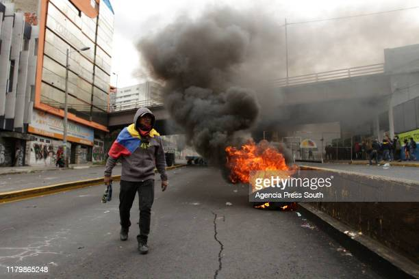 A protester walks by burning tyres at the main street that leads to the National Assembly during a protest against President Lenin's economic...
