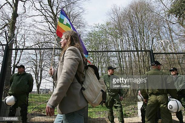 A protester walks by riot police standing guard at a section of a 14km long security fence around the German resort town of Heiligendamm which will...