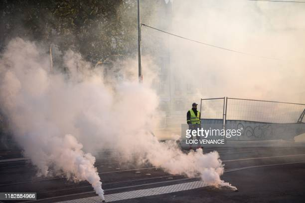 A protester walks by tear gas canisters during a demonstration marking the first anniversary of the yellow vest movement on November 16 in Nantes...