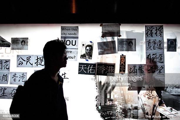 A protester walks in front of a bus stop billboard with slogan and notes in Central on October 1 2014 in Hong Kong Thousands of pro democracy...