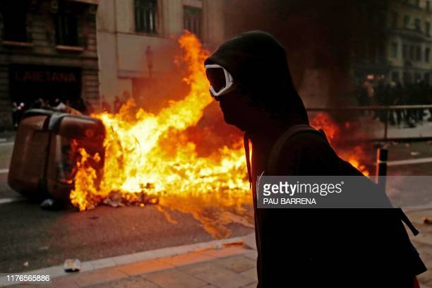 Protester walks past a burning rubbish bin near the Police headquarters in Barcelona, on October 18 on the day that separatists have called a general...