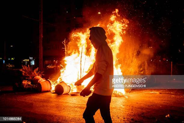 A protester walks past a fire during clashes with police at a demonstration against the government in front of the Romanian Government headquarters...