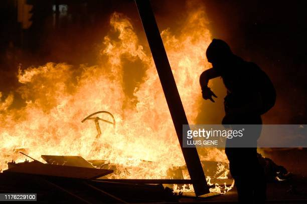 A protester walks past barricades in flames during a demonstration called by the local Republic Defence Committees in Barcelona on October 16 after...