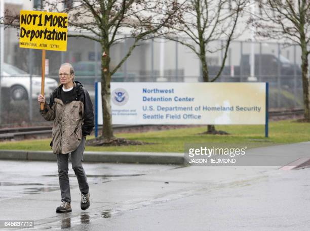 A protester walks past the entrance of the Northwest Detention Center as people attend the Peoples Tribunal Against the Detention Center event...