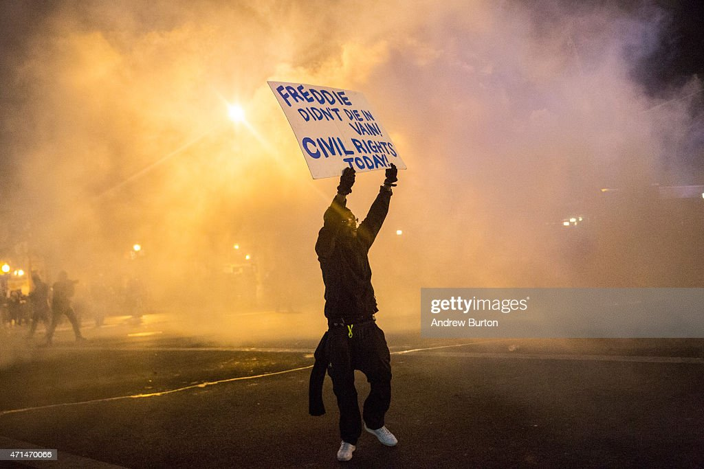 A protester walks through tear gas as police enforce a mandatory, city-wide curfew of 10PM near the CVS pharmacy that was set on fire yesterday during rioting after the funeral of Freddie Gray, on April 28, 2015 in Baltimore, Maryland. Gray, 25, was arrested for possessing a switch blade knife April 12 outside the Gilmor Houses housing project on Baltimore's west side. According to his attorney, Gray died a week later in the hospital from a severe spinal cord injury he received while in police custody.