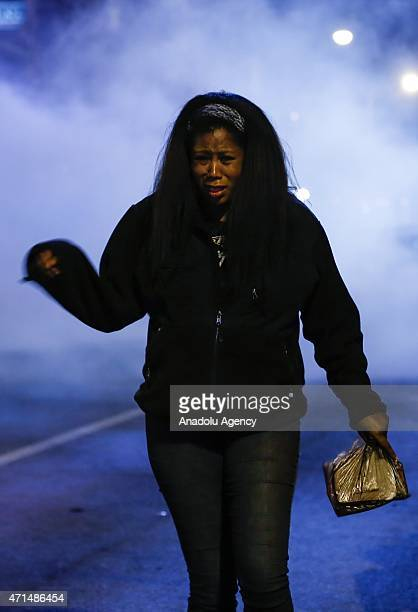 Protester walks to avoid pepper spray fired by riot police during a curfew in Baltimore, Maryland, USA on 28 April 2015. Tensions eased on 28 April...