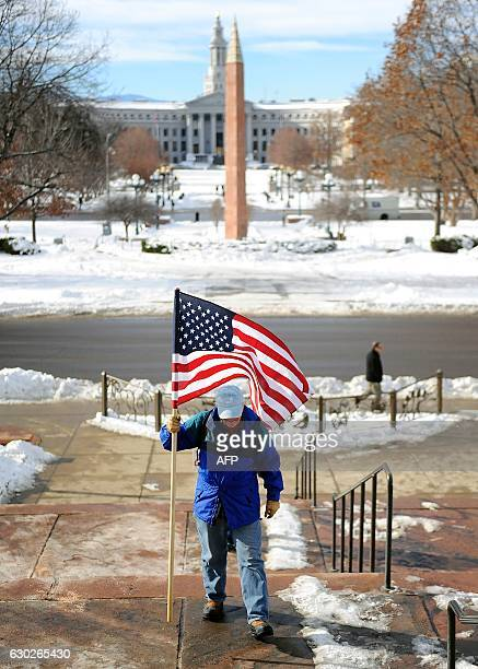 A protester walks up the steps with a US flag outside the Colorado Capitol building as a demonstration against US Presidentelect Donald Trump on the...