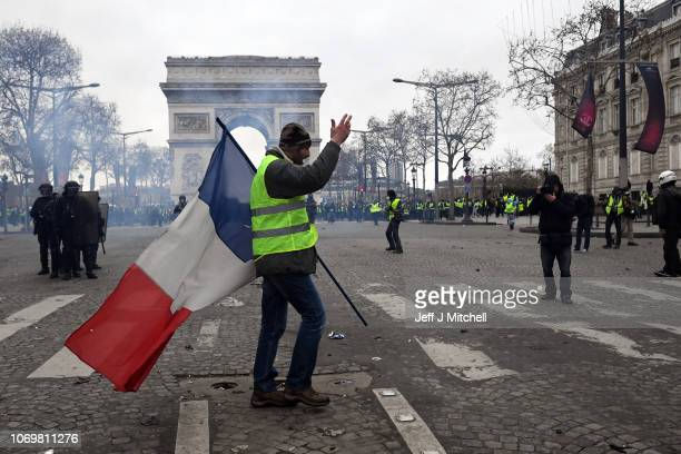 A protester walks walks with the french flag during the 'yellow vests' demonstration near the Arc de Triomphe on December 8 2018 in Paris France...