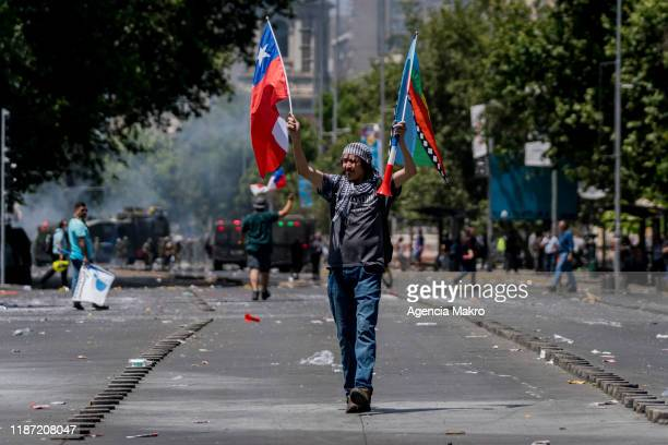 Protester walks while waving the flags of Chile and the Mapuche people during a national strike and general demonstration called by different workers...