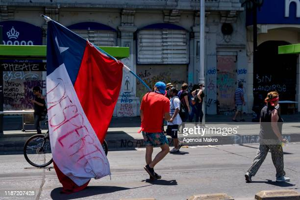 Protester walks with a Chilean flag during a national strike and general demonstration called by different workers unions on November 12, 2019 in...