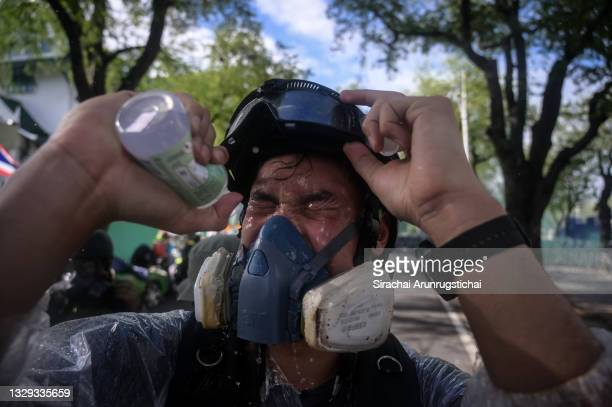 Protester washes his eyes with saline solution after police fired a water canon to try and disperse them on July 18, 2021 in Bangkok, Thailand....