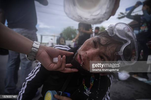 Protester washes the eyes of another with saline solution after police fired a water canon to try and disperse them on July 18, 2021 in Bangkok,...