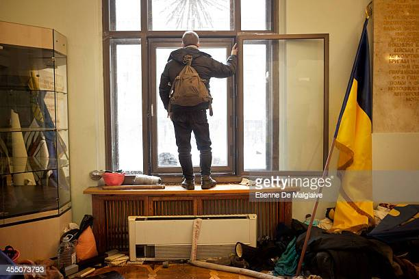 A protester watches from the City Hall building after the riot police were forced out from blocking the front door as authorities launched an early...