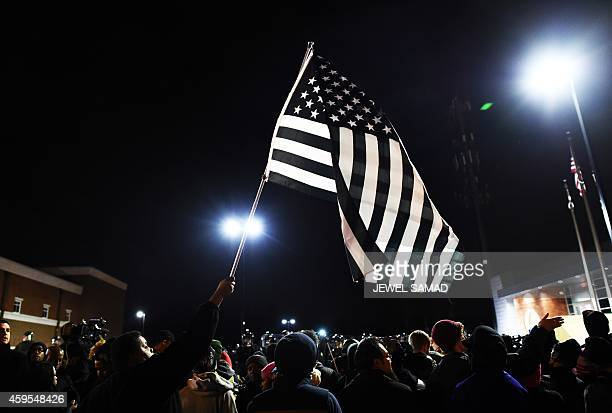 A protester waves a black and white modified US flag during a march following the grand jury decision in the death of 18yearold Michael Brown in...