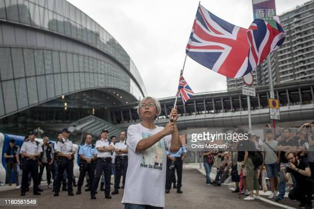 A protester waves a British flag in front of the West Kowloon railway station during a protest against the proposed extradition bill on July 7 2019...