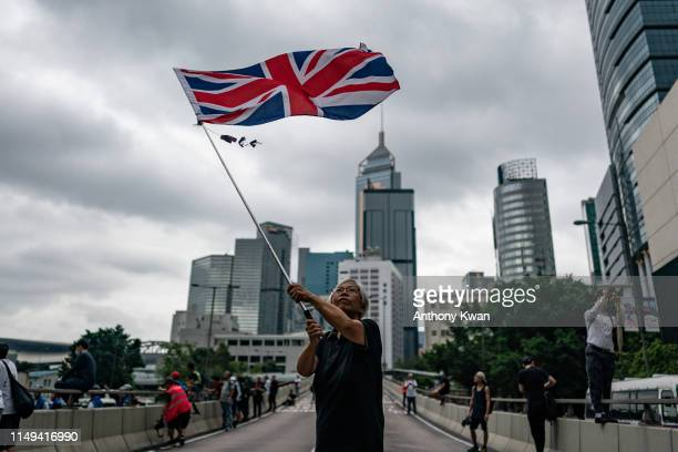 A protester waves a British flag near the government headquarters during a rally against the extradition bill on June 12 2019 in Hong Kong China...