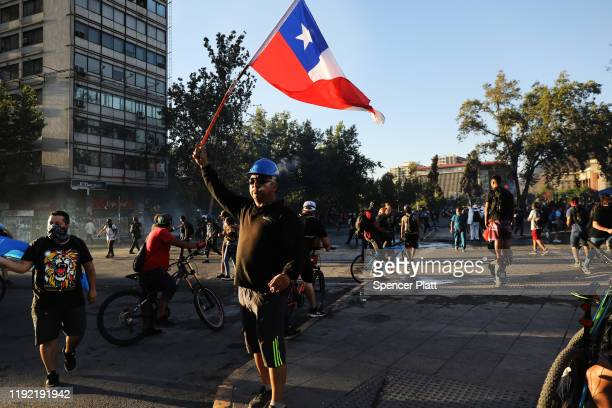 A protester waves a Chilean flag in a face off with riot police in downtown Santiago as demonstrations continue against Chilean President Sebastian...
