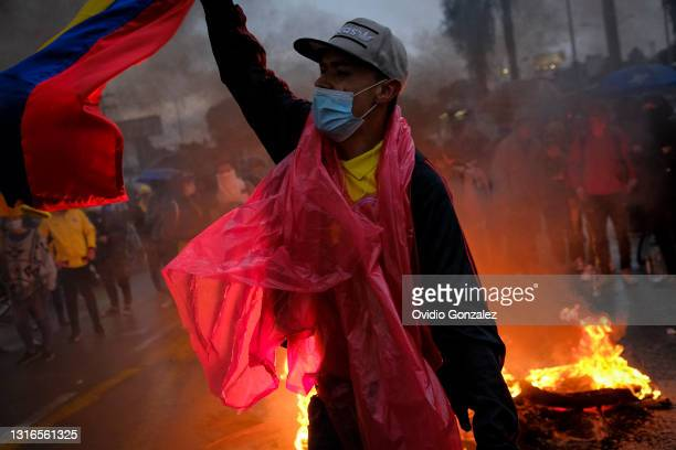 Protester waves a Colombian flag near a fire during a national strike on May 5, 2021 in Bogota, Colombia. Despite that the ruling party announced...