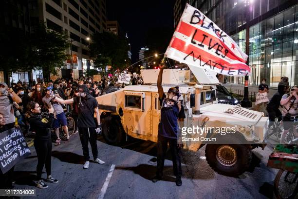 A protester waves a DC flag with Black Lives Matter spray painted on it next to a DC National Guard Humvee as protesters march through the streets...