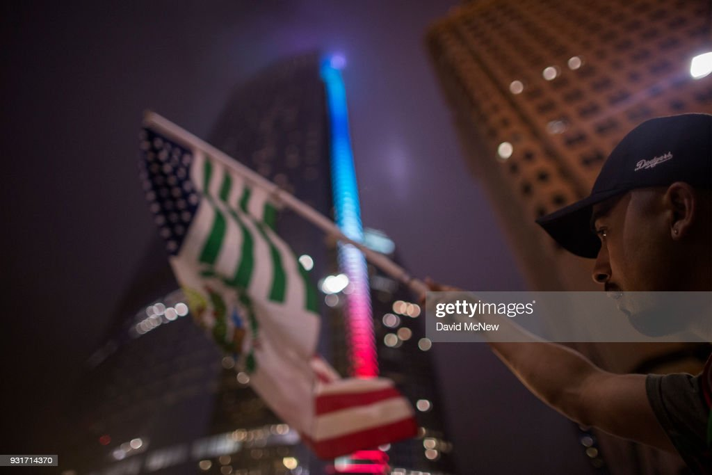 A protester waves a flag composed of elements of the U.S. and Mexican flags in front of the InterContinental Los Angeles Downtown hotel where U.S. President Donald Trump is spending the night during his first visit to California since taking office on March 13, 2018 in Los Angeles, California. Earlier today, the president visited border wall prototypes, addressed Marines and held a high-dollar fundraiser.