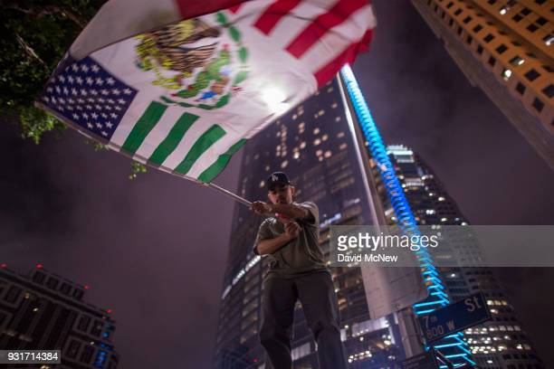 A protester waves a flag composed of elements of the US and Mexican flags in front of the InterContinental Los Angeles Downtown hotel where US...