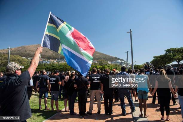 A protester waves a flag during a demonstration by South African farmers farm workers at the Green Point stadium to protest against farmer murders in...