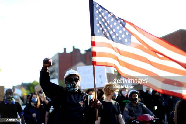 A protester waves a flag during a demonstration in response to the recent death of George Floyd on May 31 2020 in Boston Massachusetts Protests...