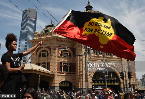 A protester waves a flag during an 'Invasion Day' rally on Australia Day in Melbourne on January 26 2018 Tens of thousands of people marched across...