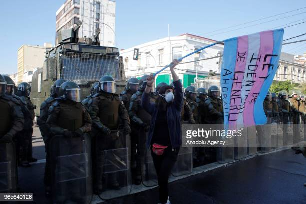 Protester waves a flag in front of security forces during a protest for the gender equality and women's rights in the surroundings of the Congress in...