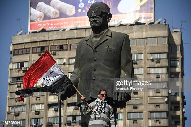 Protester waves a flag next to the famous Naguib Mahfouz statue in Cairo, on the second anniversary of the Egyptian revolution which toppled Hosni...