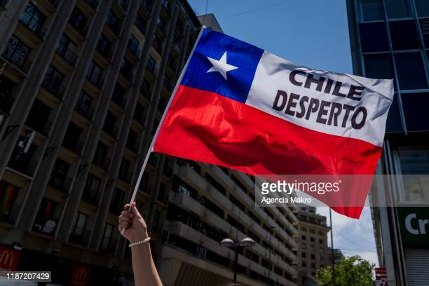 """Protester waves a flag of Chile with the phrase """"Chile has woken up"""" during a national strike and general demonstration called by different workers..."""