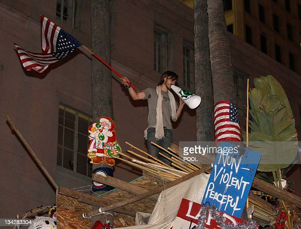 A protester waves a flag on top of a structure at the Occupy LA encampment outside City Hall in Los Angeles November 30 2011 The nearly twomonthold...