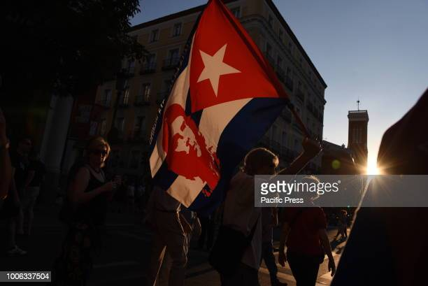 A protester waves a flag showing a portrait of Ernesto Che Guevara during the celebration of the Cuban Revolution's anniversary in Madrid