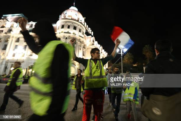 A protester waves a French flag during a protest of yellow jackets against the rising of the fuel and oil prices in front of the Negresco hotel on...