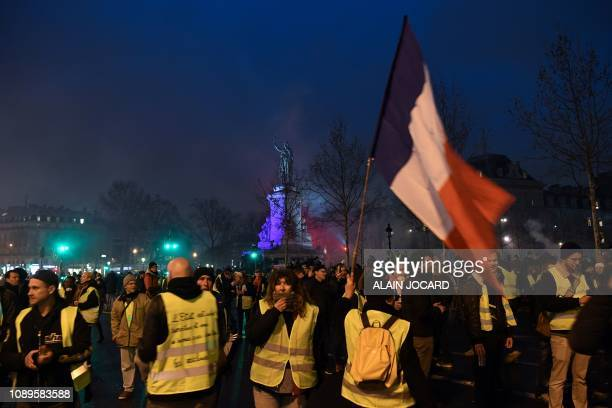 A protester waves a French flag during an antigovernment demonstration called by the yellow vests movement on the Place de la Republique in Paris on...