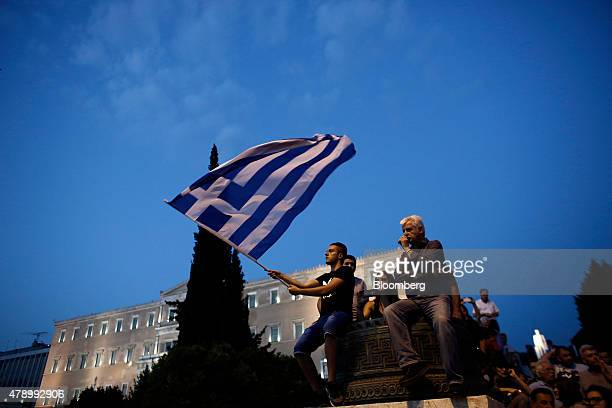 A protester waves a Greek national flag during an antiausterity demonstration in support of the Greek government in Syntagma Square in Athens Greece...
