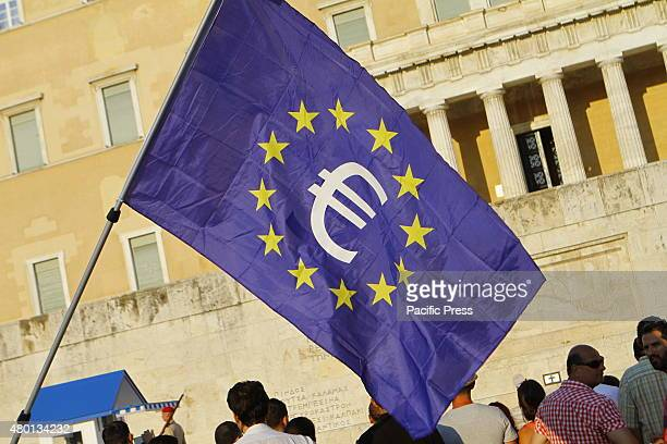 SQUARE ATHENS ATTICA GREECE A protester waves a large European flag with a Euro sign in the mittle in front of the Greek Parliament Thousands of...