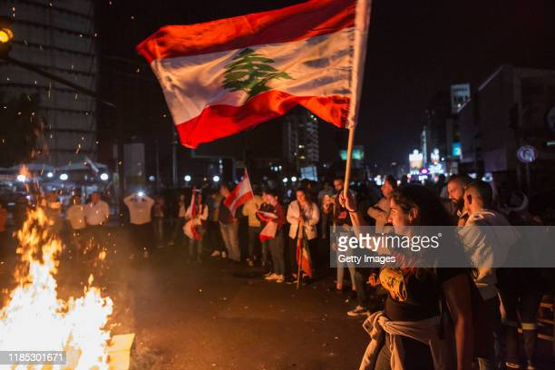 A protester waves a Lebanese flag as antigovernment demonstrators block the Chevrolet intersection on November 3 2019 in Beirut Lebanon The country...
