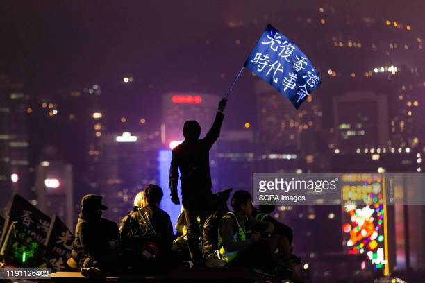 A protester waves a Liberate Hong Kong flag during the demonstrations Entering the 7th month of civil unrest protesters walked inside malls and on...
