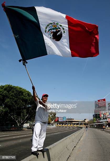 A protester waves a Mexican flag during a rally at the MexicoUnited States Port of Entry in Tijuana Mexico May 1 2006 Immigrants and their supporters...