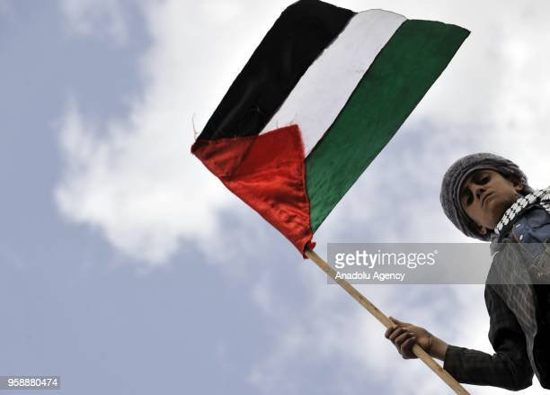A protester waves a Palestinian flag at Bab alYaman street during a protest against United States' plans to relocate the US Embassy from Tel Aviv to...