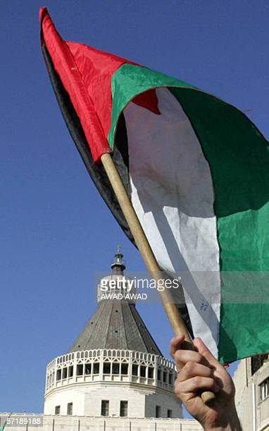 A protester waves a Palestinian flag during a demonstration in front of the Roman Catholic Church of the Annunciation in the northern Israeli town of...