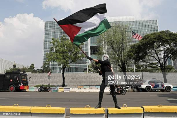 Protester waves a Palestinian flag during the demonstration. Pro-Palestinian protesters marched to the heavily guarded US Embassy in Indonesias...
