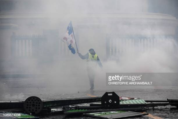 A protester waves a Picardie flag as he walks in tear gas smoke during clashes with police at an antigovernment demonstration called by the yellow...