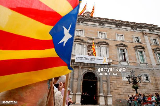 """Protester waves a pro-independence Estelada flag as a banner reading """"Free political prisoners and those exiled"""" hangs from the balcony of the..."""