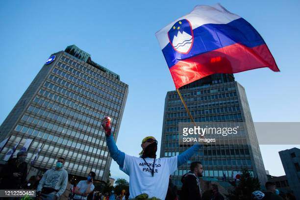 Protester waves a Slovenian flag during an anti-government protest amid the coronavirus crisis. Following whistleblower's revelations of corruption...